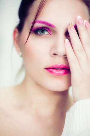 The woman with a bright pink make-up closes one eye a hand. Studio portrait. photo