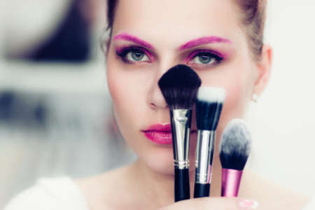make up artist: The makeup artist with bright pink make-up holds powder brushes. She covers with them the face. Studio portrait.