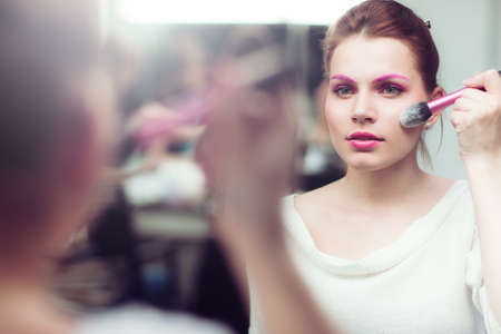 The girl with bright pink a make-up applies blush near a mirror. She touches with a brush a cheek. Studio portrait.