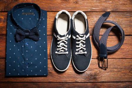 Man's collectie van kleding in casual stijl, bestaande uit een shirt met een vlinderdas, schoenen (sneakers) en riem op een houten achtergrond