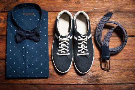 Mans collection of clothes in casual style consisting of a shirt with a bow tie, footwear (sneakers) and belt on a wooden background