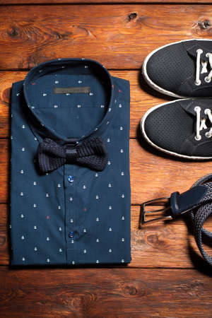 men shirt: Mans collection of clothes in casual style consisting of a shirt with a bow tie, footwear (sneakers) and belt on a wooden background