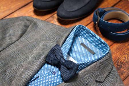 chaqueta: Hombre en traje, cinturón y zapatos sobre un fondo de madera