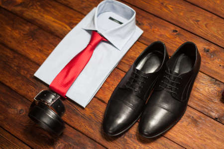 red leather texture: Mans collection: a shirt with a bright tie, shoes and a belt on a wooden background