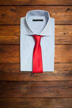 red tie: shirt with red tie on a wooden brown background