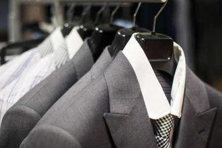 Row of mens suits hanging in closet.