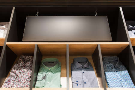 showwindow: mens casuall shirts on a showwindow and a signboard in mens clothing shop