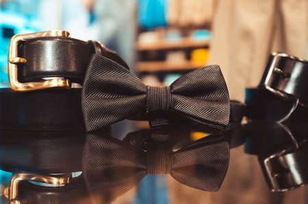 Stylish black mens tie and belt on a glass show-window of shop. set of mans accessories for a wedding