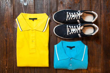 showwindow: Bright mens t-shirts (polo) and sports shoes on a dark wooden background of a show-window of shop