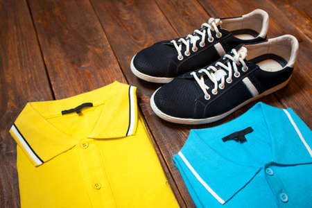 showwindow: Bright yellow and blue  mens t-shirts (polo) and sports shoes on a dark wooden background of a show-window of shop