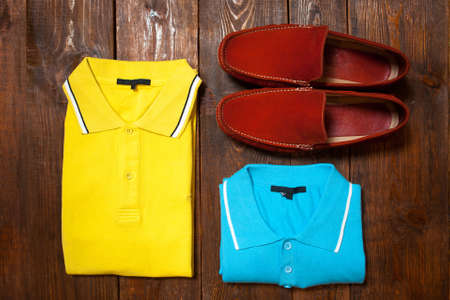moccasins: Yellow and blue mens t-shirts (polo) and red moccasins on a dark wooden background of a show-window of shop