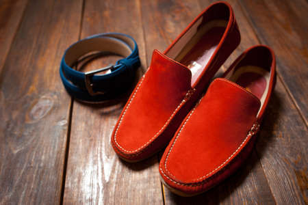 moccasins: Collection of mans accessories - new stylish bright footwear and a belt on a dark wooden background Stock Photo