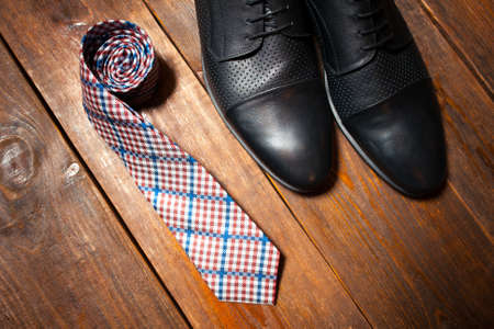 Collection of mans accessories - new leather footwear and a checkered tie on a dark wooden background Imagens