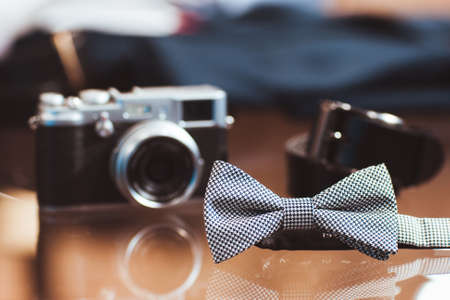 cloth background: Stylish white mens bow tie, the digital camera and belt on a glass show-window of shop. set of mans casual accessories