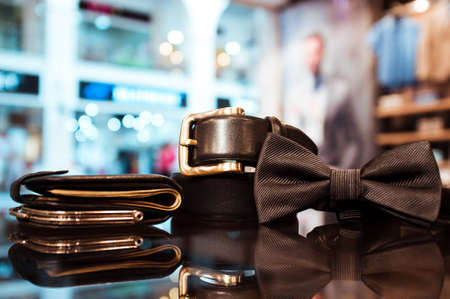 Stylish black mens tie, purse with money and a belt on a glass show-window of shop. set of business mans accessories Фото со стока