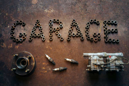 sparking plug: inscription Garage made of nuts and some automobile spare parts. Conceptual photo. Rusty metal background. Stock Photo