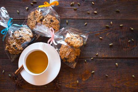 especias: taza de té de hierbas, las especias de la India y envases de regalo de las galletas de Navidad hechos en casa con frutas secas y nueces. Comida saludable. Fondo de madera oscura