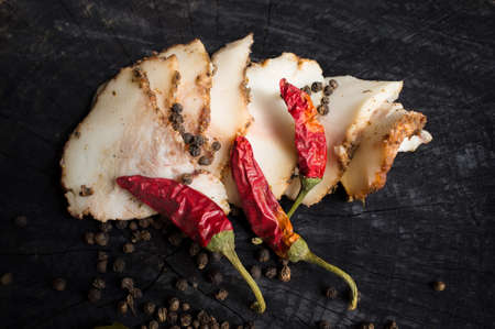 salo: Salo with spices, red pepper  and peppercorn   on the dark wooden background
