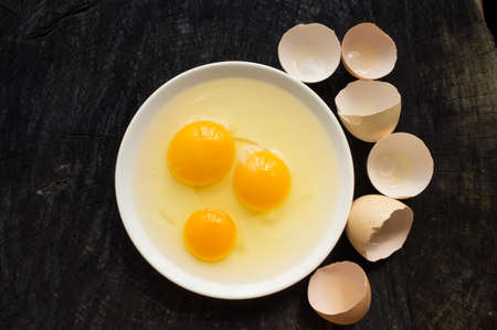 Three broken raw eggs on a white plate stand on a dark kitchen table Stock Photo