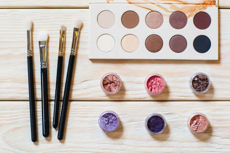 nude: set of professional brushes for a make-up of eyes, a palette of nude colored eyeshadows and colorful pigments on a wooden background. set of the professional makeup artist Stock Photo