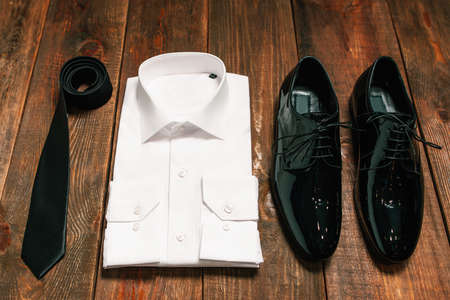 patent leather: stylish collection of mens clothing. Black tie , patent leather shoes , a white shirt - wedding set for the groom . top view. Stock Photo