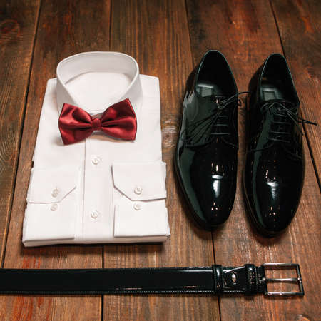 stylish collection of men's clothing. Black belt , patent leather shoes , a white shirt, marsla bowtie - wedding set for the groom . top view. Archivio Fotografico