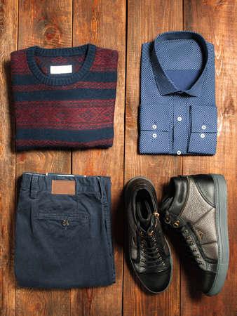 어두운 나무 배경에 남자의 따뜻한 가을 옷의 컬렉션입니다. 청바지, 셔츠, 신발, 스웨터. 인터넷 쇼핑을위한 제품. 스톡 콘텐츠
