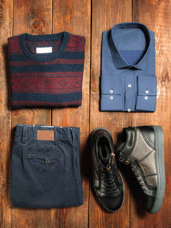 Collection of mens warm autumn clothes on a dark wooden background. jeans, shirt, shoes, sweaters. Goods for internet shop.
