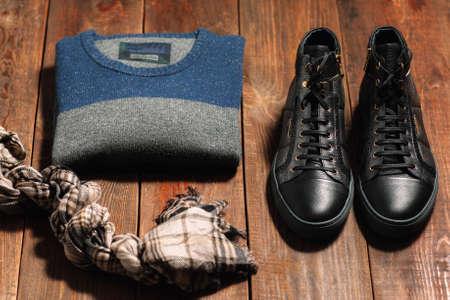 Het verzamelen van mannen warme herfst kleding op een donkere houten achtergrond. sjaal, schoenen, truien. Goederen voor de internetwinkel. Stockfoto