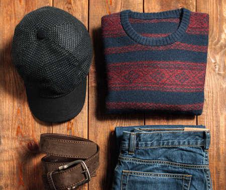 男性の暗い背景の木の暖かい秋服のコレクション。ベルト、キャップ、ジーンズ、セーター。インター ネット ショップのメンズウェア。