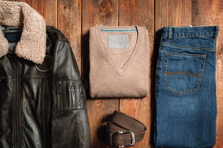 sueteres: Colección de ropa de otoño calientes de los hombres en un fondo de madera oscura. Chaqueta de invierno, pantalones vaqueros, cinturón, suéteres. Artículos para la tienda de internet.