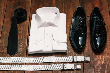 patent leather: stylish collection of mens clothing. Black tie , patent leather shoes , suspenders, a white shirt - wedding set for the groom . top view.