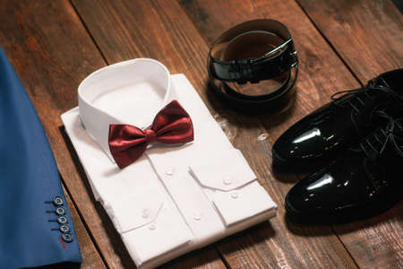patent leather: stylish collection of mens clothing. Marsala tie , patent leather shoes ,belt, a white shirt, jacket- wedding set for the groom . top view.