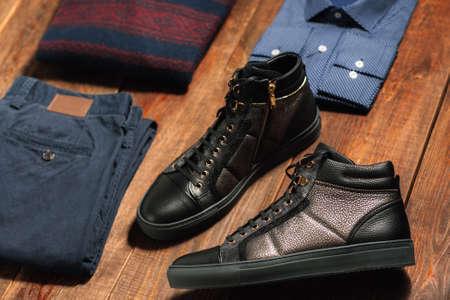 어두운 나무 배경에 남자의 따뜻한가 옷의 컬렉션입니다. 청바지, 셔츠, 신발, 스웨터. 인터넷 쇼핑을위한 남성복.