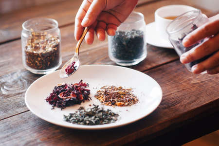 variation: several sorts of Chinese herbal tea. The waiter served a plate, mound the different types of tea (Hibiscus, green, herbal) on it. Stock Photo