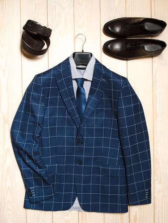 Sammlung von Tuch Männer und Zubehör in einem lässigen Stil. Draufsicht der blauen Anzug, Lederschuhe und Gürtel auf dem hellen Hintergrund aus Holz