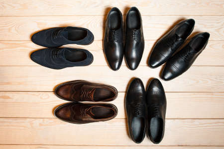a meeting with a view to marriage: Several new pair of leather shoes for men on a wooden background with plenty of free space. The concept of a business meeting. Or banner for online store