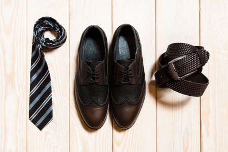 conservative: collection of mens accessories in a conservative style. top view of  tie, leather shoes and belt on the wooden background