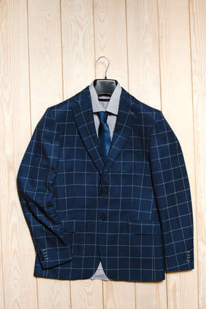 store display: stylish mens business suit with a blue pattern in a large cage. Top view on a light wooden backgroundstylish mens business suit is blue in a large square. Top view on a light wooden background Stock Photo