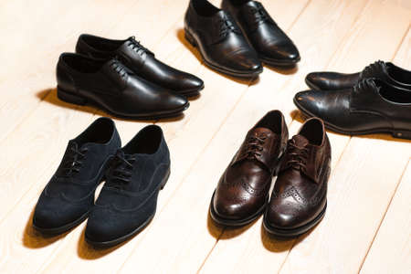 a meeting with a view to marriage: Several new pair of leather shoes for men on a wooden background with lots of free space.The concept of business meeting Stock Photo