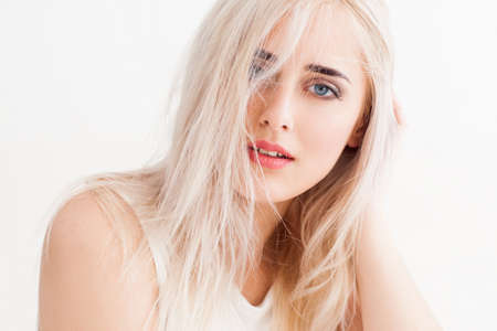 큰 파란 눈, 밝은 눈썹 자신감 금발. 그녀의 긴 흰 머리는 그녀는 침착하고 믿음으로 카메라에 보이는, 흐트러진. 흰색 배경에 스튜디오 사진입니다. 스톡 콘텐츠