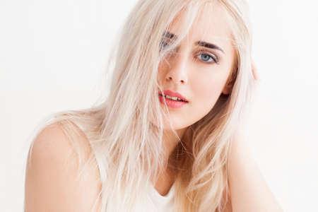 zelfverzekerde blonde met grote blauwe ogen, lichte wenkbrauwen. Haar lange witte haren slordig, ze rustig en vol vertrouwen en kijkt in de camera. studio foto op een witte achtergrond.