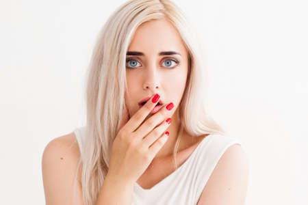 eyes wide open: Surprised girl covers her mouth and her eyes wide open. A conceptual photo on a white background