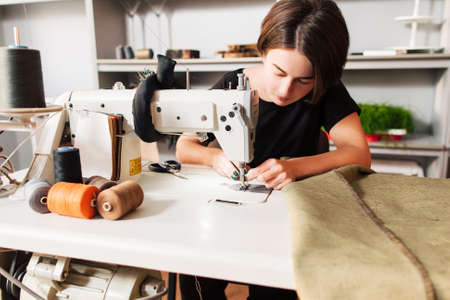costurera cose la ropa e hilo puesto en la aguja. Lugar de trabajo del sastre - máquina de coser, rollos de tela de hilo, tijeras,. Foto de archivo