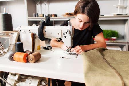 Näherin näht Kleidung und legte Faden in Nadel. Arbeitsplatz von Schneider - Nähmaschine, Rollen von Fäden, Stoff, Schere. Standard-Bild