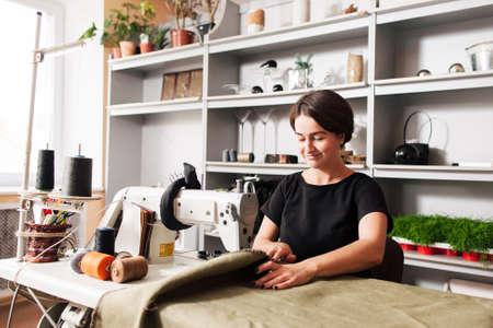 naaister naait kleren. Workplace of tailor - naaimachine, rollen van draad, stof, schaar.
