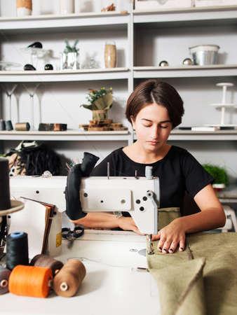 Couturière confection de vêtements. Milieu de travail de tailleur - machine à coudre, bobines de fil, tissu, ciseaux. Banque d'images - 52171740