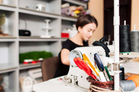 workplace: seamstress sews clothes. Workplace of tailor - sewing machine, rolls of  thread, scissors.focus on foreground Stock Photo