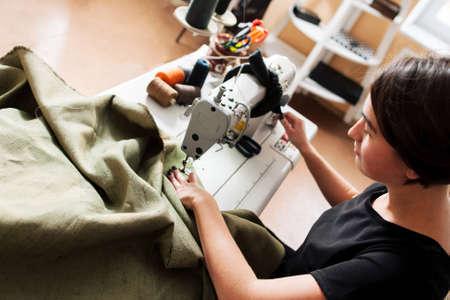 Couturière coud des vêtements. Milieu de travail de tailleur - machine à coudre, bobines de fil, tissu, ciseaux. vue de dessus Banque d'images - 52171744