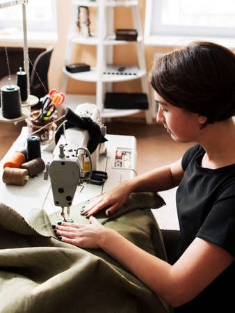 seamstress making clothes. Workplace tailor - sewing machine, rolls of  thread, fabric, scissors.
